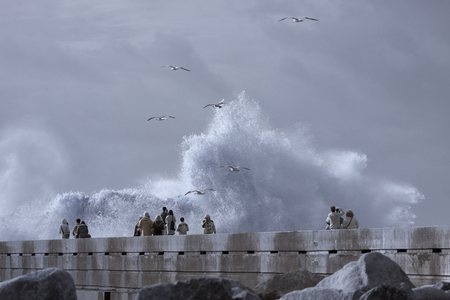People looking at the big stormy waves splashes. River Douro mouth, Porto, Portugal.