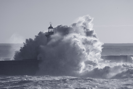Od lighthouse embraced by stormy waves. Douro river mouth, Porto, Portugal. Used infrared filter. Toned blue. Stock Photo