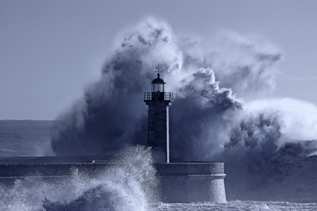 Old lighthouse in the middle of great stormy waves. Douro river mouth. Used infrared filter. Toned blue.
