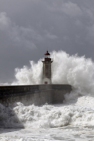 Big sea wave breaking over old pier and lighthouse of Douro river mouth against a stormy dark sky.