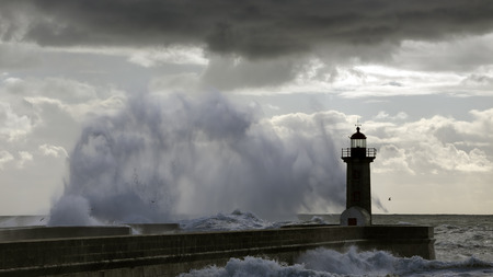 Backlit stormy sea wave splash and spray. Old lighthouse and pier of the river Douro mouth.