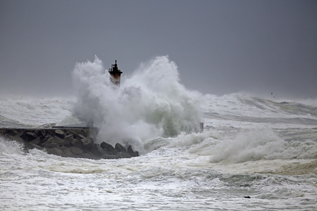 Stormy seascape from the north of Portugal seeing big wave covering beacon and pier. Stock Photo