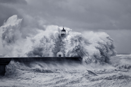 Old river Douro mouth lighthouse embrassed by huge sea waves and devastated by strong winds. Converted black and white and toned blue. Stockfoto