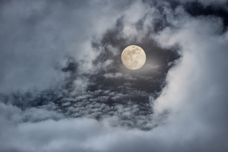 Full moon appearing behind a hole in the clouds