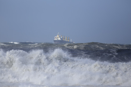 Commercial ship sailing under storm in the sea with big waves but with a beautiful blue sky