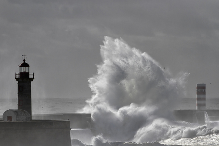 Big stormy wave splash against dark sky before rain. Douro river mouth south piers and beacons, north of Portugal.