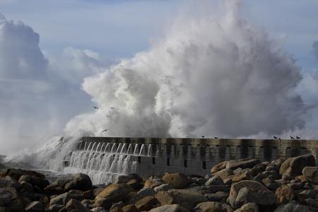 Big stormy sea wave splash. Douro river mouth north pier and beacon, Porto, Portugal.