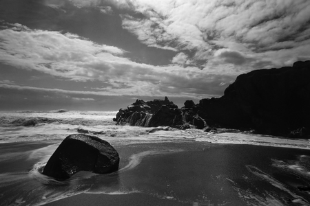 Sea cliff against deep blue sky with white clouds. Soft backlit. ANALOG: 35 mm slide film. Converted black and white.