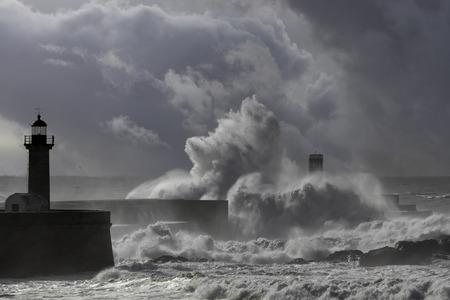 Big stormy wave splash over pier and lighthouse, Douro river mouth, porto, Portugal. Enhanced sky.