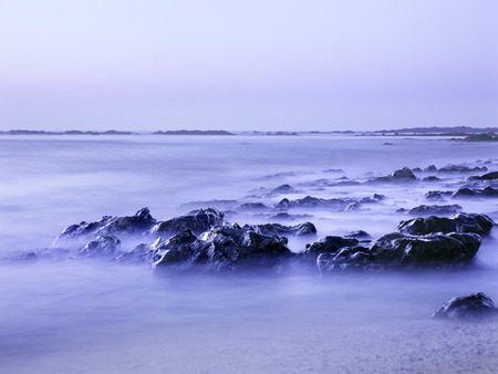 Glistening sea rocks at dusk. Long exposure. Analog: 120 film.