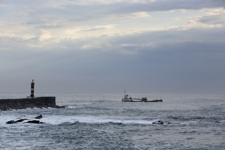 Moody seascape seeing ship, dredge, leaving the river mouth after dredging at the end of the day. North of Portugal.