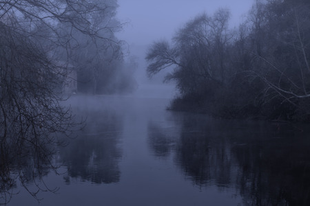 Mysterious foggy forest river at night or dusk seeing watermill. Banco de Imagens