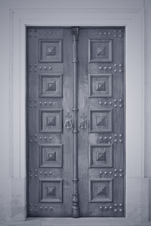 Wooden old catholic church door. Converted black and white. Toned blue.