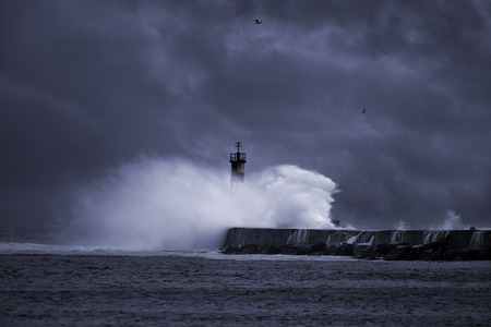 Big sea wave splash against pier and beacon from Ave river mouth, north of Portugal. Enanced sky. Toned blue.