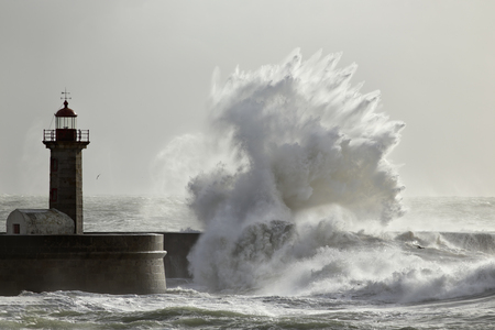 Soft backlit big stormy wave splash against pier and lighthouse in a sunny day. Standard-Bild