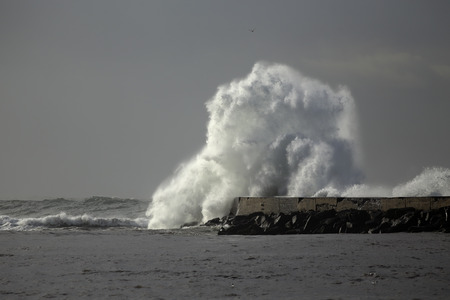 Huge stormy wave splash. Ave rive mouth pier and beacon, Vila do Conde, Portugal.