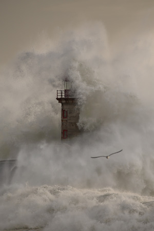 Big stormy wave splash covering old lighthouse at sunset Imagens