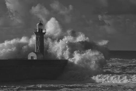 Grande spruzzi d'onda tempestosa. Vecchio faro della foce del fiume Douro, Porto, Portogallo. Filtro infrarossi usato.