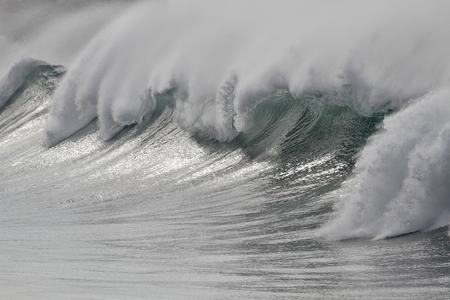 Big white breaking sea wave detail with wind spay.