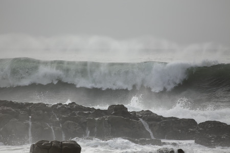 Stormy breaking sea wave with spray. Northern portuguese rocky coast.