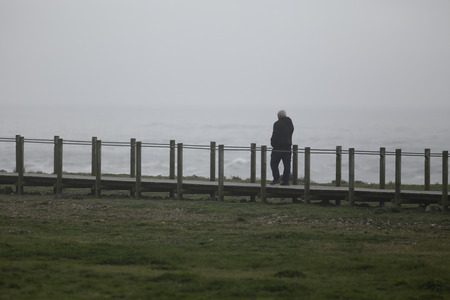 Matosinhos, Portugal - Man walking on Wooden walkway protecting the dunes along the Portuguese Coast used for walking and also as the road to São Tiago, foggy Stock Photo
