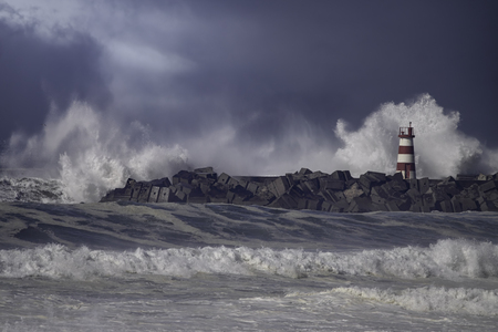 Rough sea. Beacon and pier of Povoa de Varzim harbor entry. Northern portuguese coast. Enhanced sky.