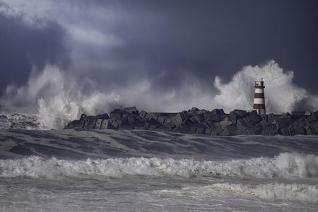 Rough sea. Beacon and pier of Povoa de Varzim harbor entry. Northern portuguese coast. Enhanced sky. 版權商用圖片 - 126223852