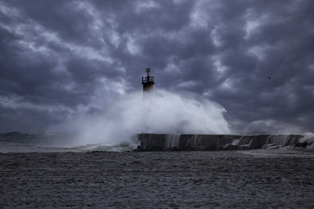 Rough sea. Beacon and pier of Ave river mouth. Northern portuguese coast. Enhanced sky. Stock Photo