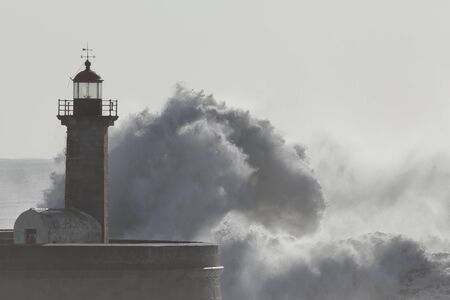 Soft backlit big wave splash. Old pier and lighthouse of Douro river mouth.