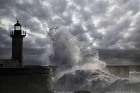Soft backlit big wave splash. Old Oporto lighthouse. Enhanced sky.