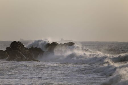 Waves breaking over cliff off northern portuguese coast at sunset