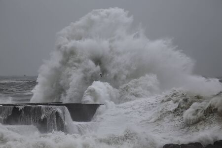 Big stormy waves and splash over pier