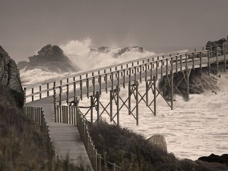 Wooden bridge over troubled waters. Photo composition.