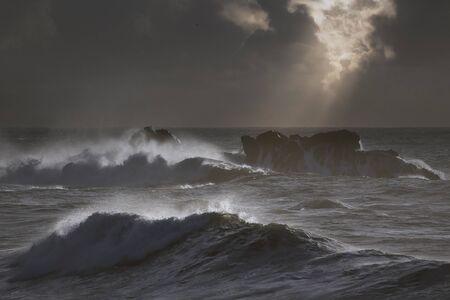 Ciemny burzliwy pejzaż morski z promieniami światła przez chmury o zachodzie słońca