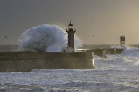 Big stormy breaking waves over Douro river mouth piers and beacons at sunset