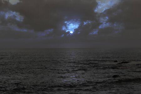 Dark cloudy full moon night at sea Фото со стока