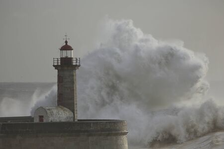 Big breaking sea waves over Douro river mouth old pier and lighthouse Stockfoto