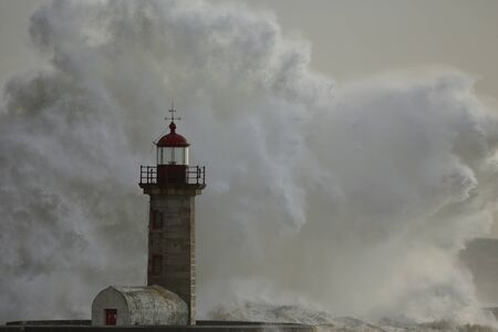 Huge stormy sea wave splash. Douro river mouth old lighthouse.