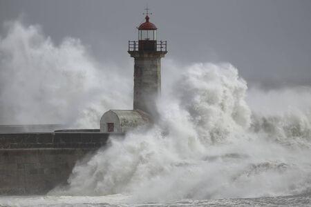 Sea storm. Douro river old lighthouse, Porto, Portugal.
