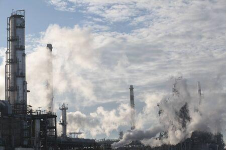 Partie d'une grande raffinerie de pétrole au milieu de la vapeur d'eau et contre un beau ciel bleu avec des nuages blancs Banque d'images