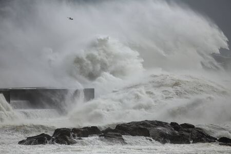 Stormy waves splash and wind spray against ocean pier from northern Portugal.