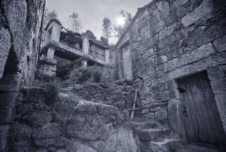 Ruin of old country agriculture house and his granary. North of Portugal. Toned blue. ANALOG: 35mm film. Stock Photo