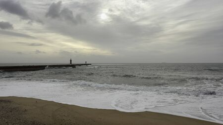 Oporto overcast seascape. Douro river mouth south piers and beacons.