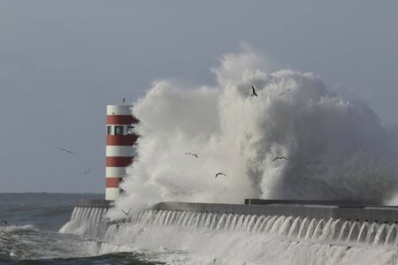 Big wave splash against pier and beacon Stockfoto