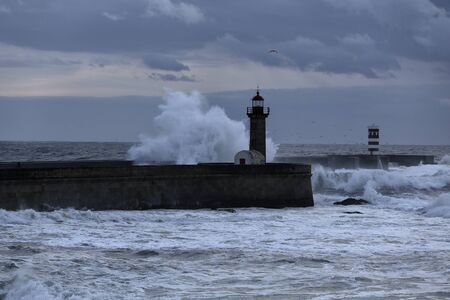 Dramatic seascape at dusk. Douro river mouith north piers and beacons during a sea storm. Stock fotó