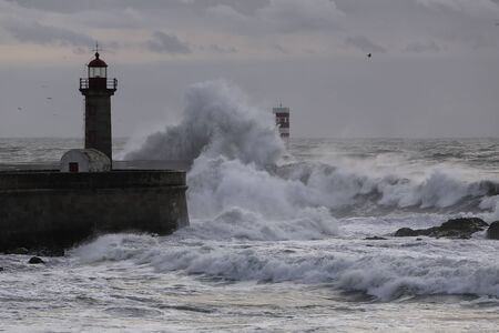 Dramatic seascape at dusk. Douro river mouith north piers and beacons during a sea storm.