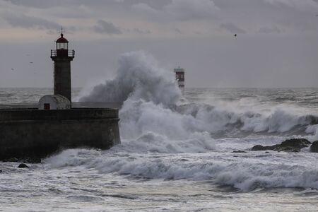 Drammatica vista sul mare al tramonto. Moli e fari a nord della foce del fiume Douro durante una tempesta di mare.