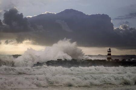 Entry of Povoa do Varzim and Vila do Conde harbor in a rough sea evening. North of Portugal. Enhanced sky.