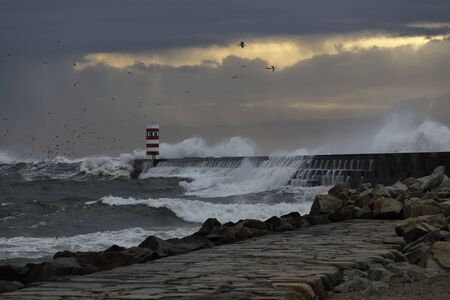 Dramatic stormy winter sunset at the Douro river mouth north pier and beacon.