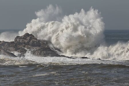 Big wave splash in a stormy but sunny morning. Northern portuguese rocky coast.